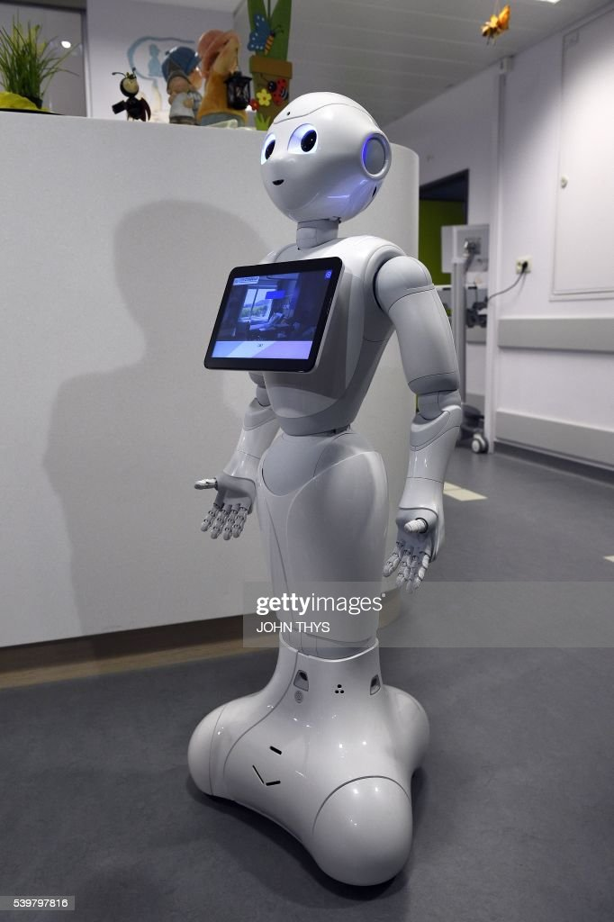 A photo taken on June 13, 2016 shows the robot Pepper during a press conference oat the CHR Citadel hospital centers of Liege. the CHR Citadel hospital centers of Liege and AZ Damiaan of Ostend will welcome next week a humanoid robot intended to guide and to inform the visitors who appear in their entrance hall. The new robot on which these hospitals decided to buy, conscript Pepper, is more tall(140 cms), more mobile and more adapted to the missions of hospitality. It was adapted to the specific expectations of the healthcare professionals to support the teams ready in the posts of reception. / AFP / JOHN