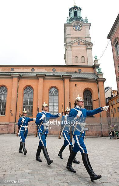 Photo taken on June 15 2010 shows soldiers marching for the change of the palace guard with the Stockholm cathedral Storkyrkan behind them Two men...