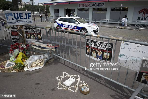 A photo taken on June 26 2015 shows a police car parked behind metal barriers outside the Hypercacher kosher supermarket at Porte de Vincennes in...