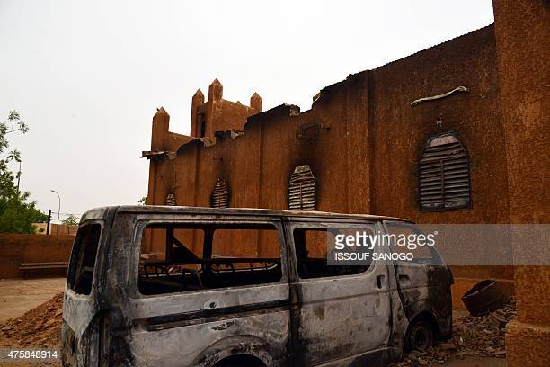 Photo taken on June 3, 2015 shows a burned car outside the burned ruins of a Baptist church in Niamey which was damaged in January 2015 after it was...