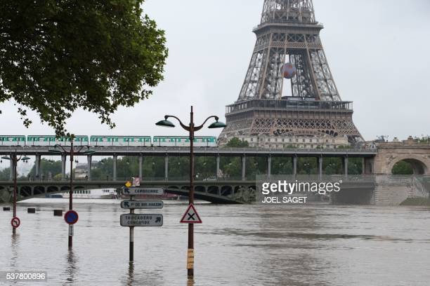 A photo taken on June 3 2016 in Paris shows a part of the Eiffel tower and a subway crossing a bridge over the river Seine after its banks became...
