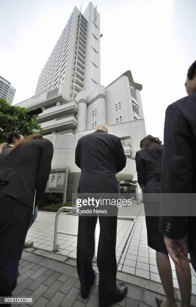 Photo taken on June 3 shows Schindler Elevator KK President John Bundy offering prayers over a fatal accident involving one of the company's...