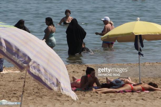 A photo taken on June 4 2015 shows two Muslim women wearing Chador as they enjoy their time with other people a beach of Narbonne southern France The...