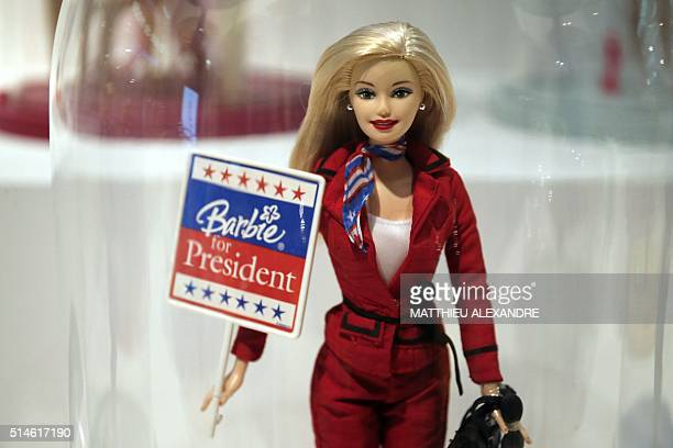 A photo taken on March 10 2016 in Paris shows a Barbie doll holding an electoral poster reading Barbie for president during the exhibition Barbie...