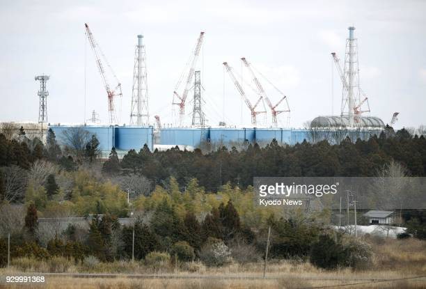 Photo taken on March 10 2018 shows cranes at the crippled Fukushima Daiichi nuclear power plant in Okuma a Fukushima Prefecture town within an...