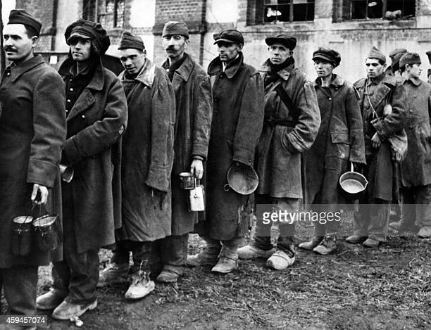 A photo taken on March 15 1945 in a nazi concentration camp liberated by Allied troops shows deportees waiting in line to receive food The prisoners...