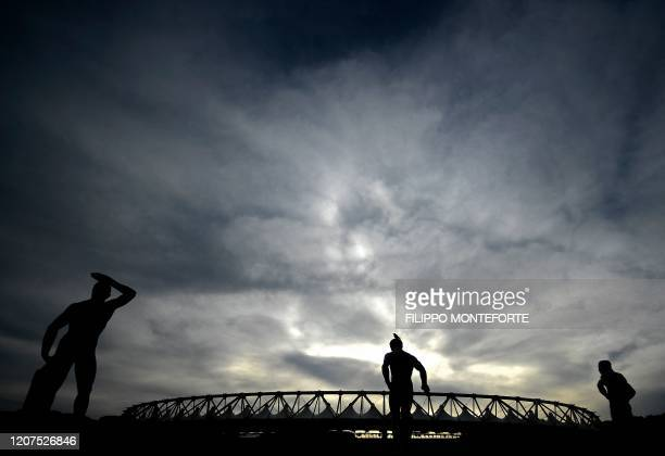 Photo taken on March 17, 2020 shows the Olympic stadium in Rome, with statues from the Marbles stadium in foreground. - The European EURO 2020...
