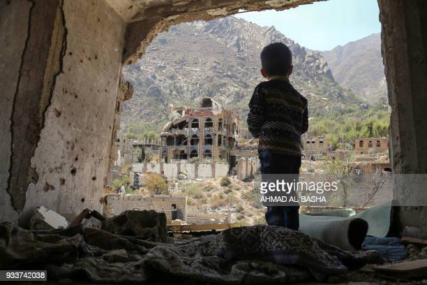 TOPSHOT A photo taken on March 18 shows a Yemeni child looking out at buildings that were damaged in an air strike in the southern Yemeni city of...