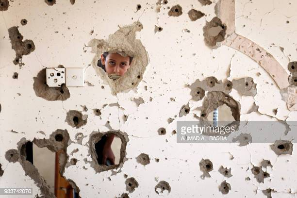 A photo taken on March 18 shows a Yemeni child looking out from behind a wall that was damaged in an air strike in the southern Yemeni city of Taez /...