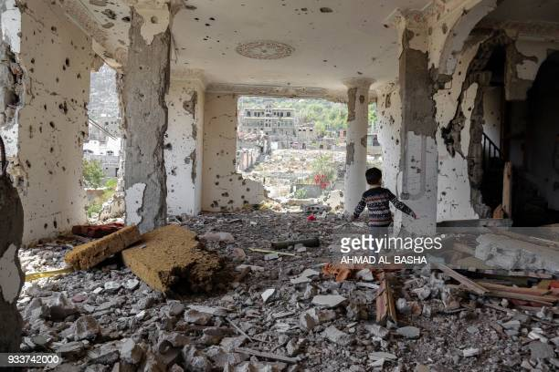 TOPSHOT A photo taken on March 18 shows a Yemeni child walking in the rubble of a building that was destroyed in an air strike in the southern Yemeni...