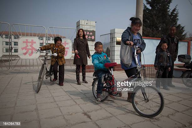 A photo taken on March 21 2013 shows parents and children leaving a school in Chengde Hebei province a town where inhabitants are not bound by the...