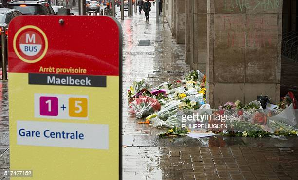 Photo taken on March 25, 2016 shows wreaths of flowers on the ground near the Maalbeek subway station in Brussels in homage to the victims of a...