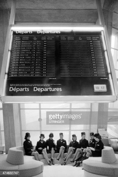 Photo taken on March 8 1974 shows flight attendants sitting under a departures screen at the checkin area during the inauguration of the new airport...