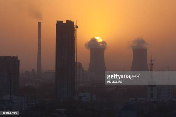 A photo taken on March 9 2013 shows the sun setting behind chinmeys rising above the skyline of Baoding Hebei province some 140 km south of Beijing...