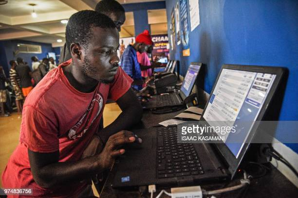 A photo taken on May 13 2018 shows a man betting on European football games at sports betting shop in Kampala Uganda On a dark potholed street next...