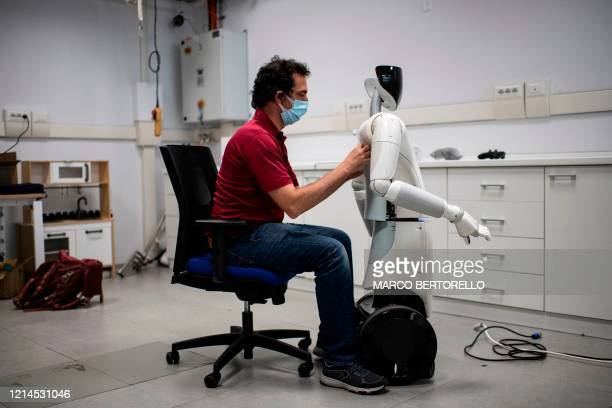 TOPSHOT A photo taken on May 21 2020 shows an engineer working on R1 a robot designed to operate in domestic and professional environments at the...
