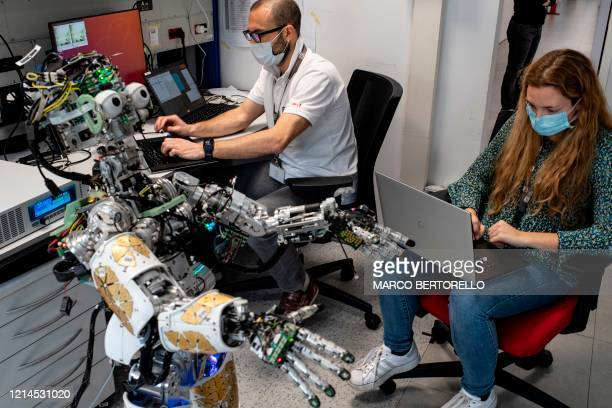 A photo taken on May 21 2020 shows engineers wearing a face mask working on iCub an open source cognitive humanoid robot at the Italian Institute of...