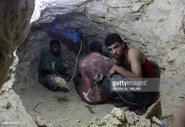 A photo taken on May 29 2014 shows opposition fighters digging in a tunnel in the Bustan alBasha neighbourhood of the northern Syrian city of Aleppo...
