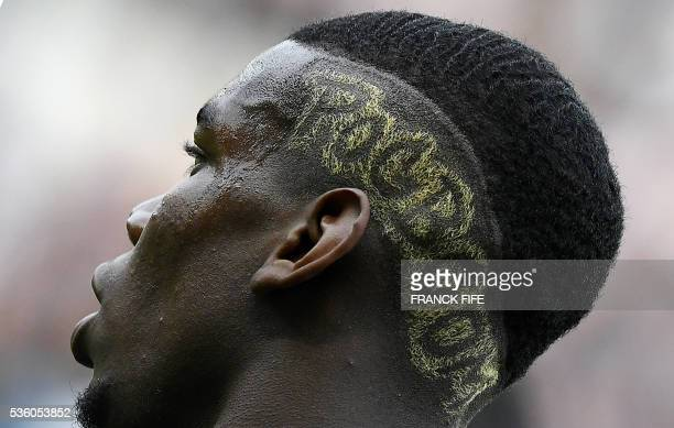 A photo taken on May 30 2016 shows a detail of France's midfielder Paul Pogba's haistyle during the friendly football match between France and...