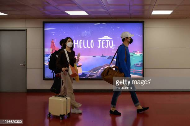 A photo taken on May 31 2020 shows travellers wearing face masks walking past a poster inside Jeju airport on Jeju island