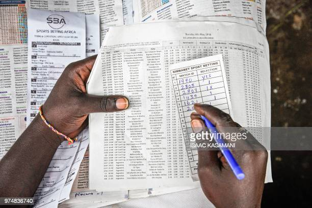 A photo taken on May 6 2018 shows a man bets on European football games at sports betting shop in Kampala Uganda On a dark potholed street next to...