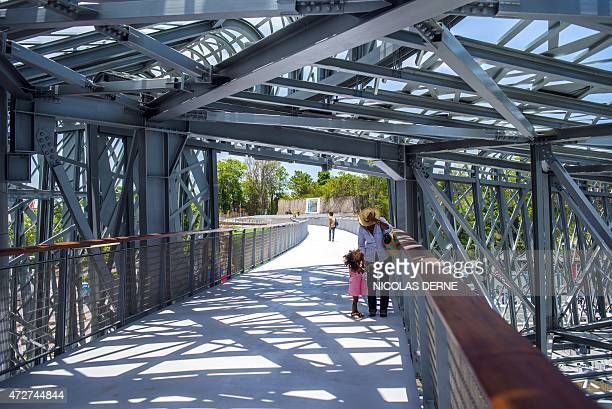A photo taken on May 8 2015 shows a women and a young girl on a footbridge designed by architect Marc Mimram at the Memorial ACTe the Caribbean...