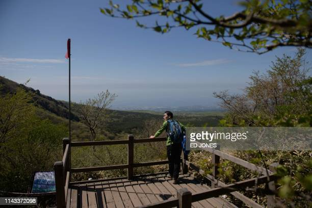 A photo taken on May 9 2019 shows a hiker at a viewpoint on Hallasan or Halla mountain on Jeju island The volcanic Hallasan is South Korea's tallest...