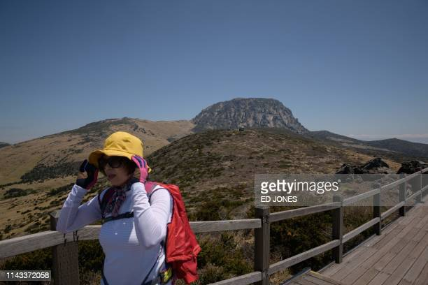 A photo taken on May 9 2019 shows a hiker walking before the peak of Hallasan or Halla mountain on Jeju island