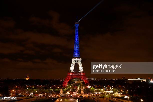 A photo taken on November 16 2015 in Paris shows the Eiffel Tower illuminated with the colours of the French national flag in tribute to the victims...