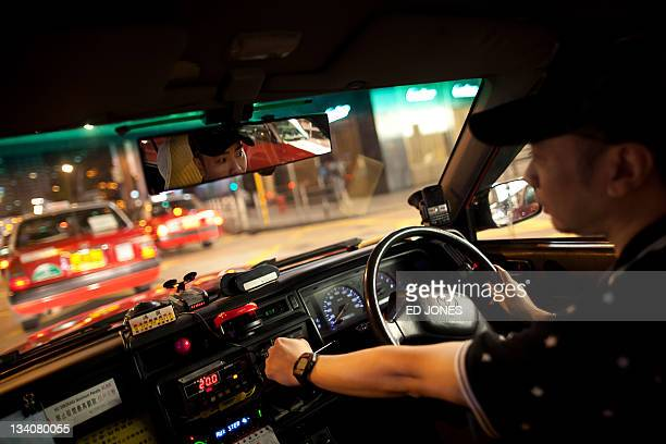 A photo taken on November 19 2011 shows taxi driver Alan Leung at the wheel of his cab in Hong Kong As rush hour approaches the streets of Hong Kong...