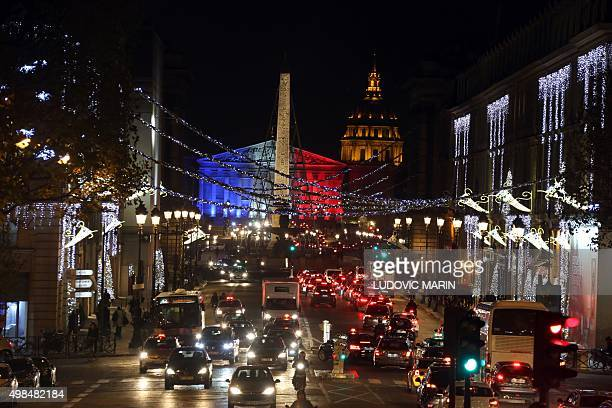 A photo taken on November 23 2015 in Paris shows traffic moving along Rue Royale decorated with Christmas lights and the National Assembly...