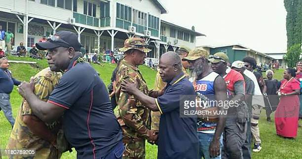 Photo taken on November 6 2019 shows former Bougainville Revolutionary Army fighters hugging Papua New Guinea policemen at a Bougainville...