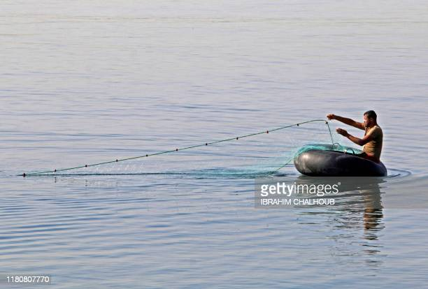 A photo taken on November 8 2019 shows a fisherman casts his net into the sea off the coast of the northern port city of Tripoli