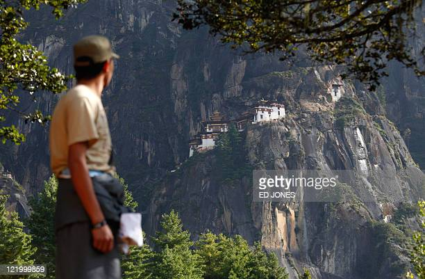 Photo taken on October 1 2010 shows a Bhutanese man standing before the Taktsang Dzong also known as the Tiger's Nest monastery near Paro Bhutan...