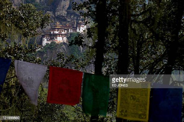 Photo taken on October 1 2010 shows prayer flags flying before the Taktsang Dzong also known as the Tiger's Nest monastery near Paro Bhutan Built in...