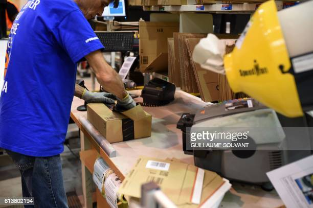 A photo taken on October 10 2016 shows a worker packing an item at the Amazon distribution center in Saran / AFP / GUILLAUME SOUVANT