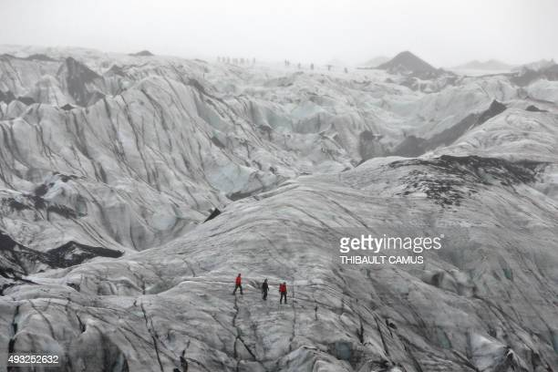 A photo taken on October 16 2015 shows tourists walking on the Solheimajokull glacier where the ice has retreated by more than 1 kilometer since...