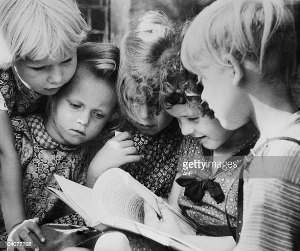 A photo taken on October 1957 shows young schoolgirls reading a book AFP PHOTO