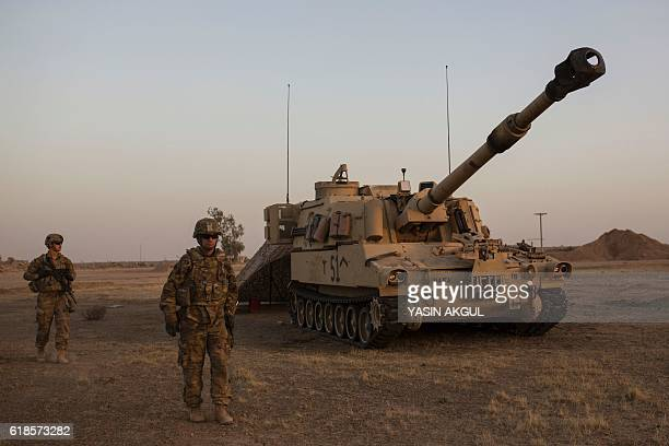 A photo taken on October 20 2016 shows a US soldier walking past a tank at the Qayyarah military base during the ongoing operation to recapture the...