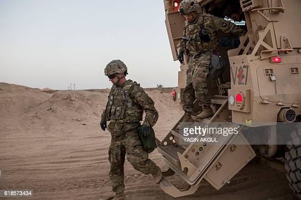 A photo taken on October 20 2016 shows US soldiers getting out of a military vehicle at the Qayyarah military base during the ongoing operation to...