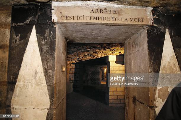 A photo taken on October 2014 at the Paris catacombs of Paris shows a corridor with the inscription 'Stop Here is the empire of death' The...