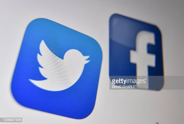 Photo taken on October 21, 2020 shows the logo of the the American online social media and social networking service, Facebook and Twitter on a...