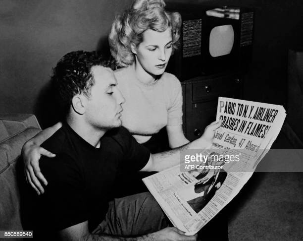 Photo taken on October 31 1949 shows US boxer Jake LaMotta and his wife Vikki reading the newspaper announcing the death of Marcel Cerdan just as he...