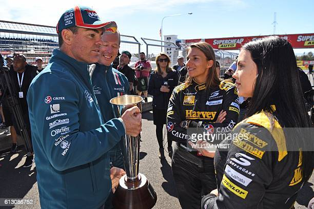 A photo taken on October 5 2016 shows Swiss driving ace Simona de Silvestro and codriver Australian Renee Gracie chatting with fellow drivers Craig...