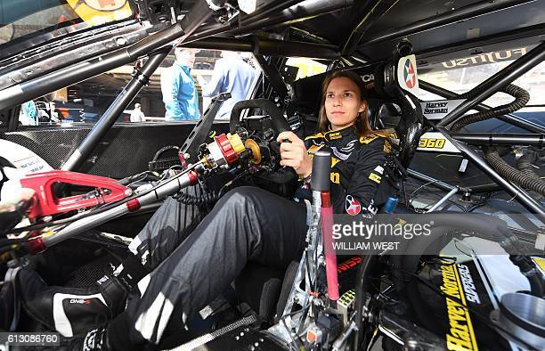 A photo taken on October 5 2016 shows Swiss driving ace Simona de Silvestro sitting behind the wheel of her race car as she and codriver Australian...