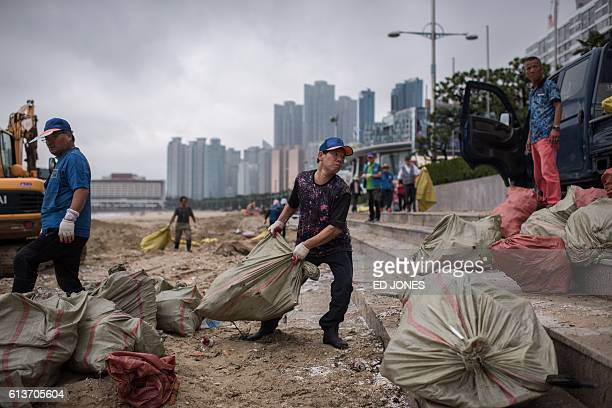 A photo taken on October 8 2016 shows workers clearing typhoon debris from Haeundae beach from temporary installation that were due to be used as...