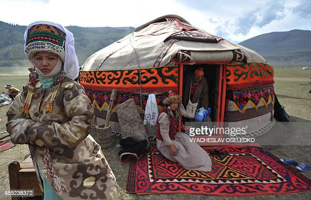 Photo taken on September 10 2014 shows a Kyrgyz woman in traditional Kyrgyz dress near the yurta during the first World Nomad Games in the Kyrchin...