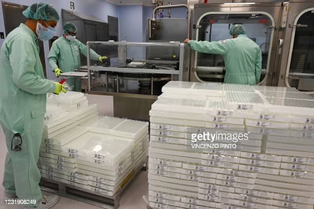 Photo taken on September 11, 2020 shows laboratory technicians handling vials as part of filling and packaging tests for the large-scale production...