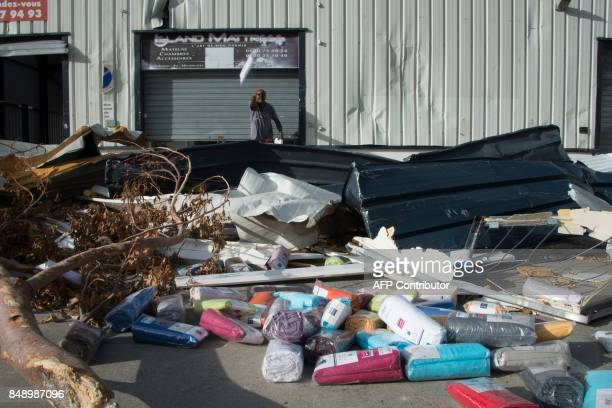 A photo taken on September 17 2017 shows a shopkeeper removing the few undamaged items from his depot in an industrial zone in Hope Estate on the...