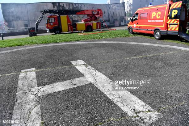 A photo taken on September 21 2017 in Grenoble eastern France shows firefighter vehicles in front of a hangar of the French gendarmerie devastated by...